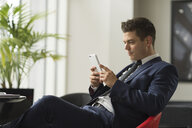 Businessman sitting in office looking at smartphone - CUF12290