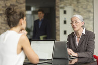 Mature businesswoman and female colleague having discussion over office desk - CUF12302
