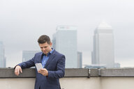 Businessman looking at smartphone on city office roof terrace, London, UK - CUF12311