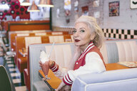 Portrait of mature woman in baseball jacket with milkshake in 1950's diner - CUF12320