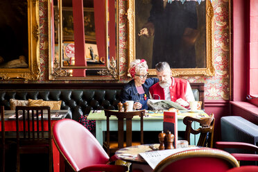 Quirky couple relaxing in bar and restaurant, Bournemouth, England - CUF12374