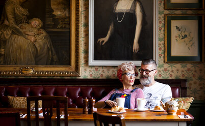 Quirky couple relaxing in bar and restaurant, Bournemouth, England - CUF12377