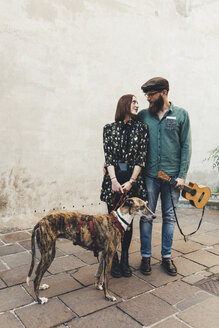 Cool couple with dog and ukulele on sidewalk - CUF12413
