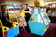 Couple enjoying themselves in amusement arcade, Bournemouth, England - CUF12437