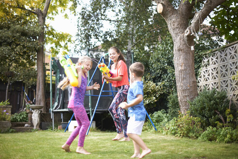 Boy and his sisters having water gun fight in garden - CUF12464