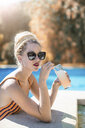 Young woman with dreadlocks, relaxing beside swimming pool, holding cold drink - CUF12482