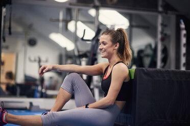 Happy young woman training, sitting on gym floor - CUF12539