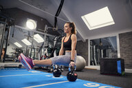 Young woman training, doing sit up push ups on kettle bells in gym - CUF12542