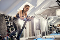 Young woman training, pedalling exercise bike in gym - CUF12545