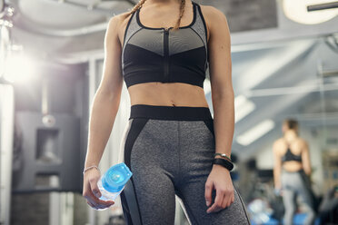 Mid section of young woman training, holding water bottle in gym - CUF12548