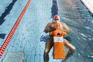 Senior man preparing lifesaving training equipment in swimming pool - CUF12611
