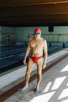 Senior man standing by swimming pool - CUF12617