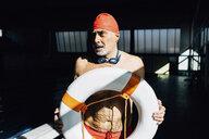 Senior man on lifeguard duty holding float - CUF12626