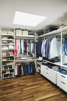 Walk-in his and hers closet with skylight window, American walnut flooring on the upstairs floor inside a modern cube style home, Quebec, Canada - ISF02098