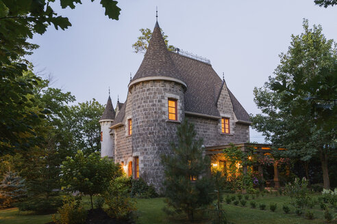 2006 reproduction of a 16th century grey stone and mortar Renaissance castle style residential home facade, at dusk, in summer, Quebec, Canada - ISF02101