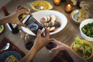 Hands of female friends taking photograph of meal at kitchen table - ISF02104