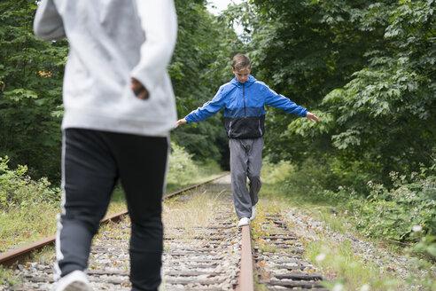 Teenage boys walking on railway track, Pacific Rim National Park, Vancouver Island, Canada - ISF02113