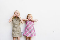 Portrait of two cute sisters pulling faces in front of white wall - CUF12936