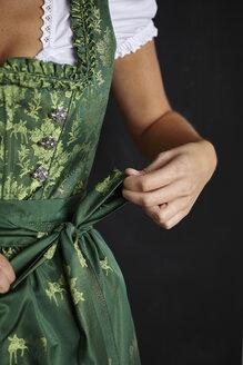 Young woman tying Dirndl apron - CUF13110