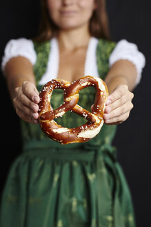 Young woman in Dirndl holding pretzel - CUF13116