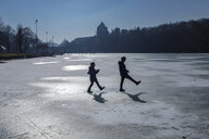 Two children playing on icy surface - HAMF00322