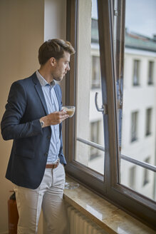 Businessman with cup of coffee looking out of window - BEF00095