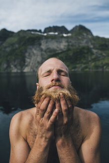Man washing his beard at a lake with eyes closed - GUSF00799