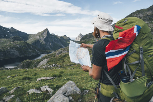 Norway, Lofoten, Moskenesoy, Man with backpak and Norwegian flag holding map - GUSF00808
