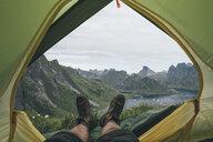 Norway, Lofoten, Moskenesoy,  Feet of man, lying in a tent over Kjerkefjord - GUSF00820