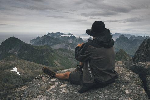 Norway, Lofoten, Moskenesoy, Young man sitting at Hermannsdalstinden, looking over Kjerkefjord - GUSF00826