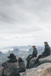 Norway, Lofoten, Moskenesoy, Young men sitting at Hermannsdalstinden, looking over Kjerkefjord - GUSF00829