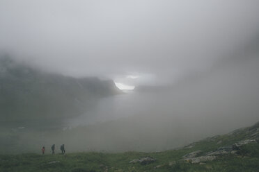 Norway, Lofoten, Moskenesoy, Three men hiking in the fog - GUSF00850