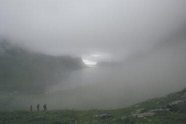 Norway, Lofoten, Moskenesoy, Three men hiking in the fog - GUSF00850