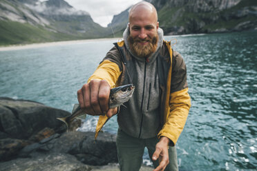 Norway, Lofoten, Moskenesoy, Young man holding freshly caught fish - GUSF00862