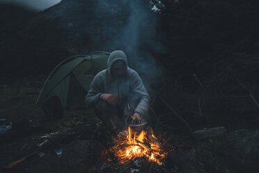 Norway, Lofoten, Moskenesoy, Young man sitting at camp fire - GUSF00871