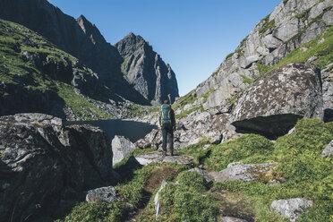 Norway, Lofoten, Moskenesoy, Young man standing in front of Litljordtinden - GUSF00880