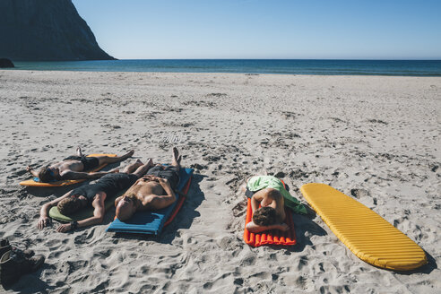 Norway, Lofoten, Moskenesoy, Friends sunbathing on Kvalvika Beach - GUSF00883