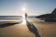 Norway, Lofoten, Moskenesoy, Man walking into the sun at Kvalvika Beach - GUSF00889