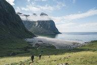 Norway, Lofoten, Moskenesoy, Young men hiking at Kvalvika Beach - GUSF00901