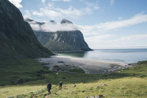 Norway, Lofoten, Moskenesoy, Young men hiking at Kvalvika Beach - GUSF00901