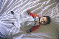 Portrait of smiling baby girl wearing jumpsuit lying on bed - GEMF01996
