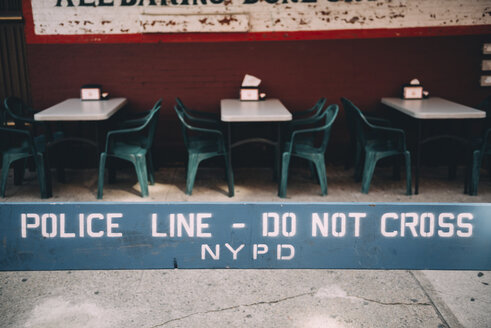USA, New York, New York City, Poline line, do not cross, empty street restaurant in the background - GEMF01999