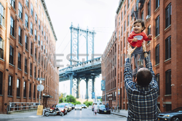 USA, New York, New York City, Father playing with baby in Brooklyn with Manhattan Bridge in the background - GEMF02002 - Gemma Ferrando/Westend61