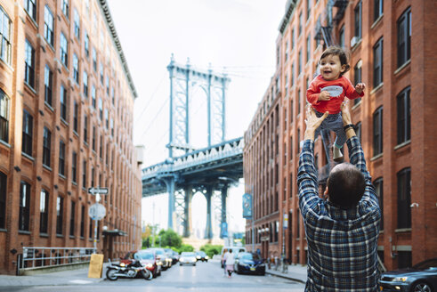 USA, New York, New York City, Father playing with baby in Brooklyn with Manhattan Bridge in the background - GEMF02002