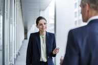 Portrait of smiling businesswoman listening to business partner - DIGF04308