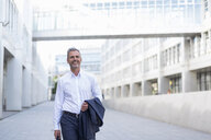 Portrait of smiling businessman walking at courtyard of modern office building - DIGF04320