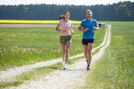 Couple running on field path - DIGF04347