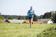 Mature man running on meadow - DIGF04353