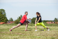 Couple doing stretching exercise on meadow - DIGF04356