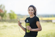 Sportive woman using smartphone during cooling break - DIGF04362